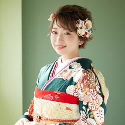 青緑の振袖を着た笑顔の女性