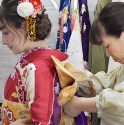 帯を結んでもらっている振袖姿の女性