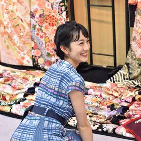 いくつもの鮮やかな振袖の生地が並んでいる前で嬉しそうな表情を浮かべる女性