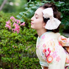花の香りを楽しむ振袖の女性