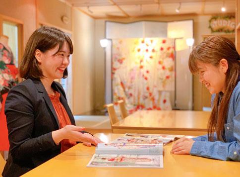 振袖のパンフレットを見せてもらっている笑顔の女性