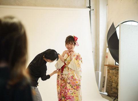 撮影スタジオで振袖を整えてもらっているはにかんだ笑顔の女性