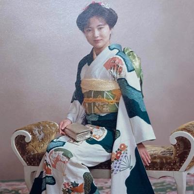 椅子に腰かけた振袖姿の笑顔の女性