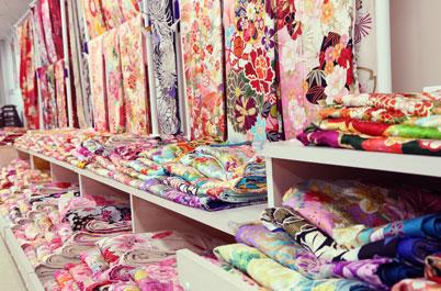 とみひろ 振袖いちばん館 仙台店の棚に畳まれた色とりどりの鮮やかな振袖の生地