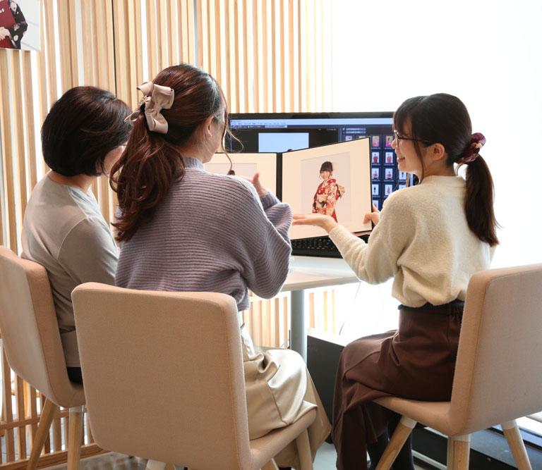 フェリーク 青山店で完成した振袖のアルバムを笑顔の店員に見せてもらっている母と娘