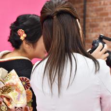 撮影してもらった写真をカメラで確認させてもらっている笑顔の振袖姿の女性