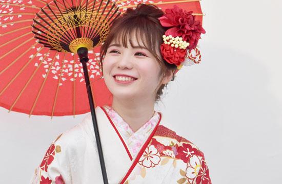 番傘をさした振袖姿の笑顔の女性